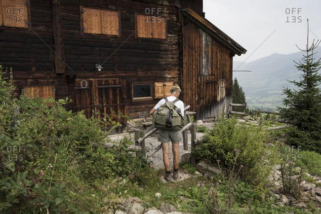 Hiker standing at wooden house- Jochberg- Austria