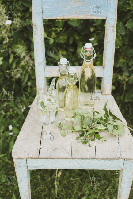 Bottled peppermint juice and glass on a chair