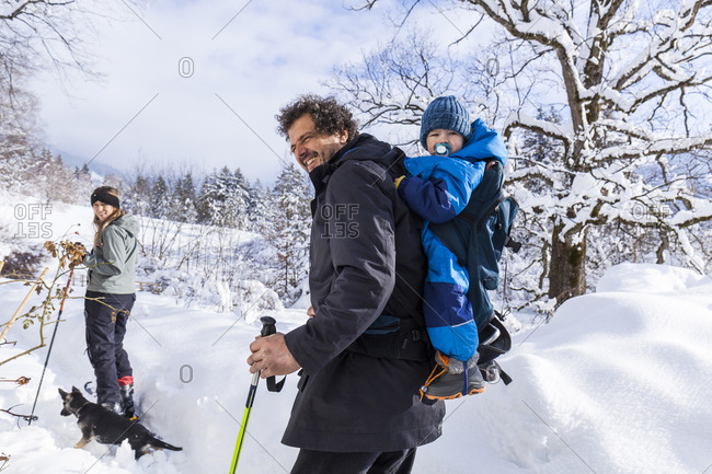 Father with son in the child carrier- mother and dog in Oberammergau in winter