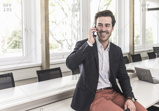 Young businessman sitting in boardroom- talking on the phone