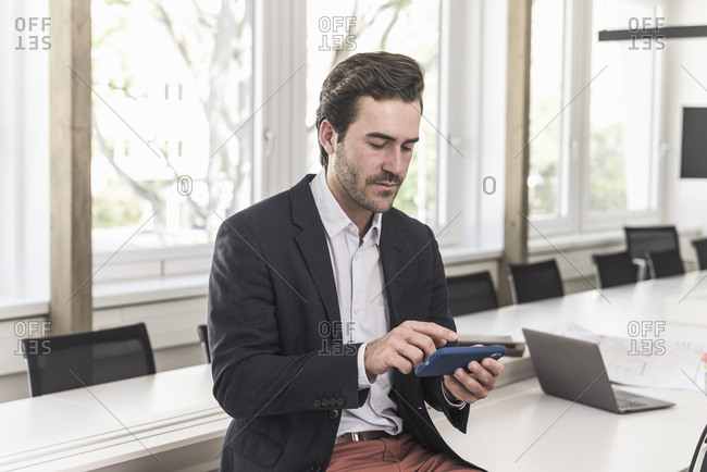 Young businessman sitting in boardroom-usig  smartphone