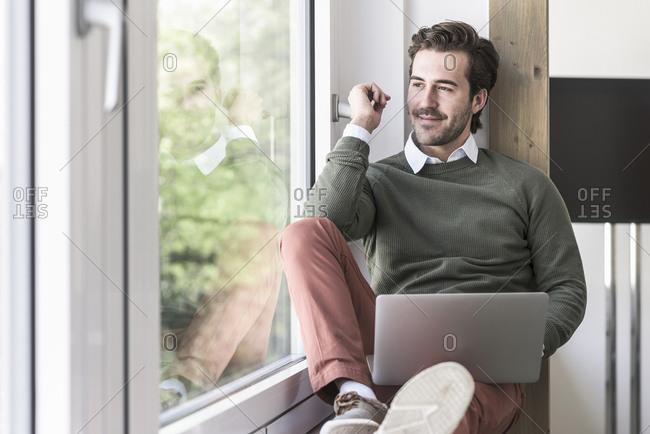 Young businessman sitting on windowsill- using laptop