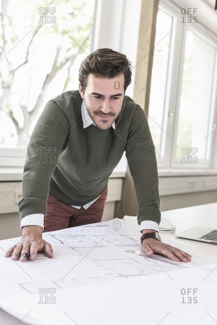 Young architect working on blueprint in bright office
