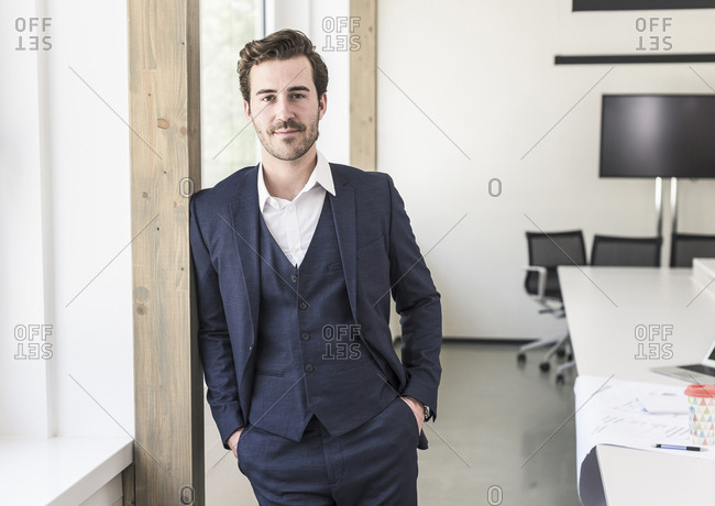 Confident businessman standing in boardroom