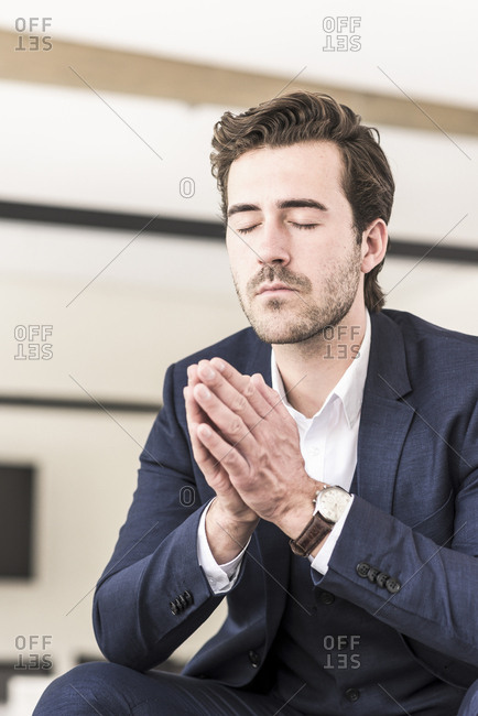 Young businessman praying with eyes closed