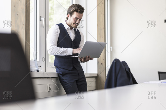 Businessman standing at the window- using laptop