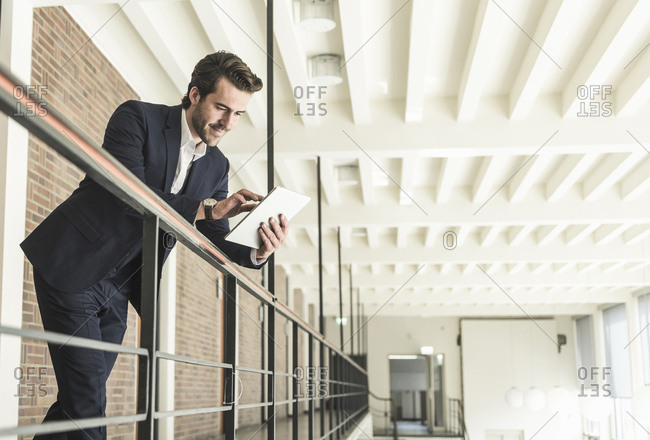 Young businessman standing on gallery in modern office building- using digital tablet