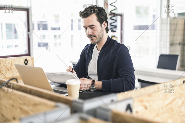 Young businessman working in coworking space- using laptoop