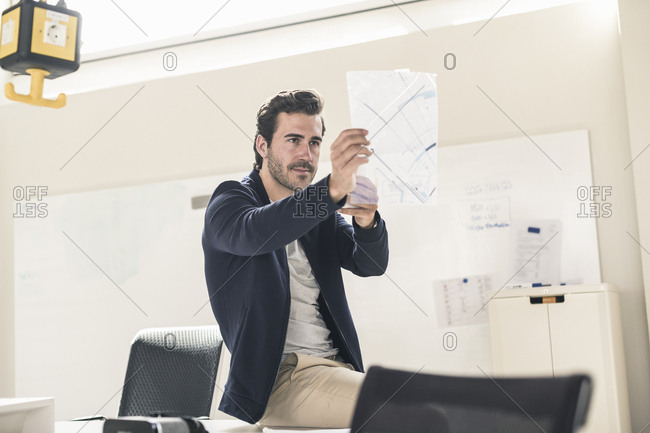 Young businessman in office holding foil of a blueprint