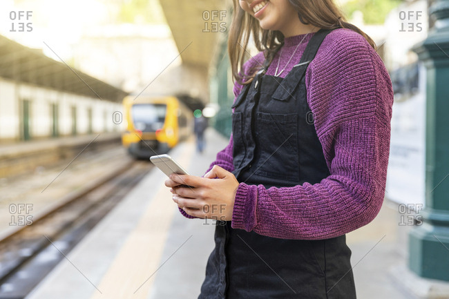 Young woman standing on platform using smartphone- Porto- Portugal