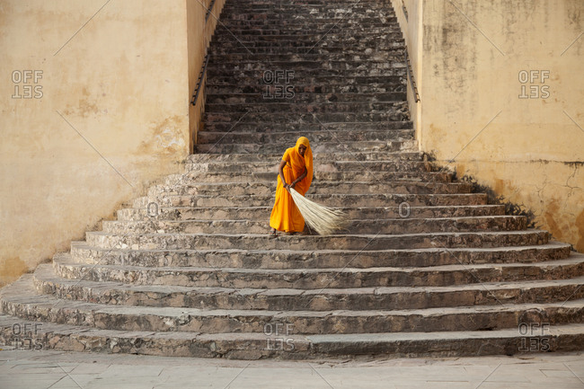 Jaipur, India - October 24, 2011: Woman cleaning stairs at Amber Fort