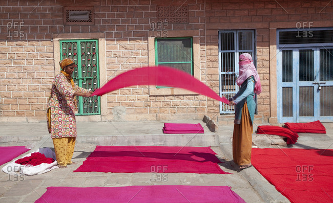 Jaipur, India - October 27, 2011: Two textile workers folding and lying cloth to dry in sun