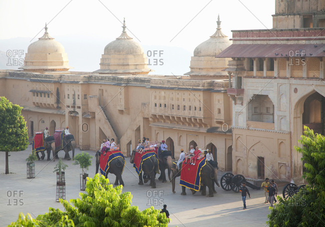 Jaipur, India - October 24, 2011: Tourists on elephants visiting Amber Fort