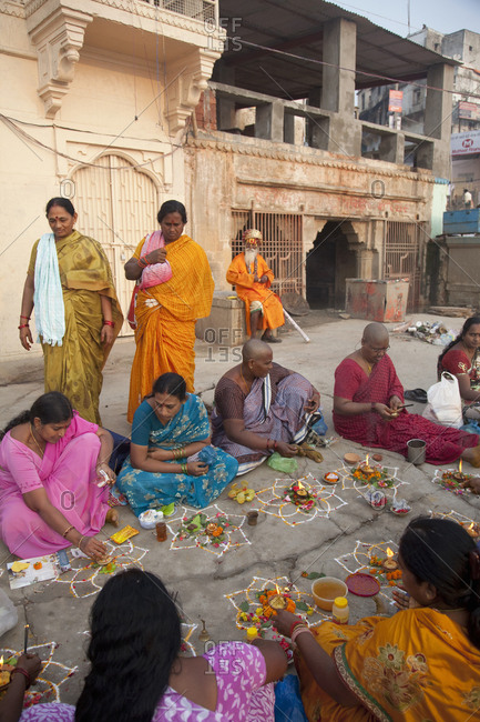 Varanasi, India - October 30, 2011: Women practicing Hindu religion rituals near banks of Ganges River