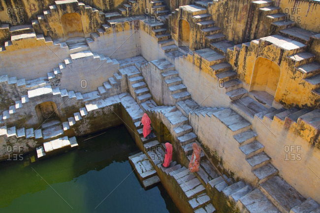 Women walking down to collect water from ancient step well near Amber fort, Jaipur, India