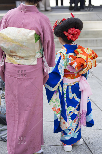 Mother and girl at Meiji Jingu shrine for prayers, Tokyo, Japan
