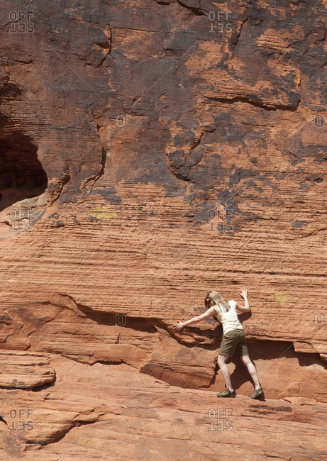 Nevada, USA - April 24, 2011: Young woman climber on rock face in Valley of Fire State Park