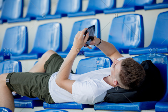 Young teenager with mobile phone lying on chairs in a stadium