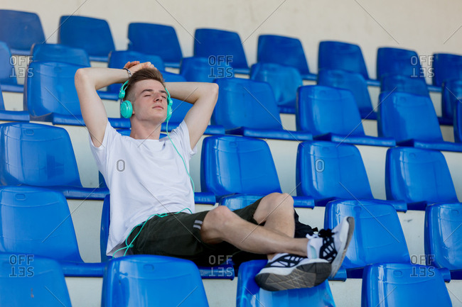 Young teen boy with headphones sitting in blue seat at a stadium