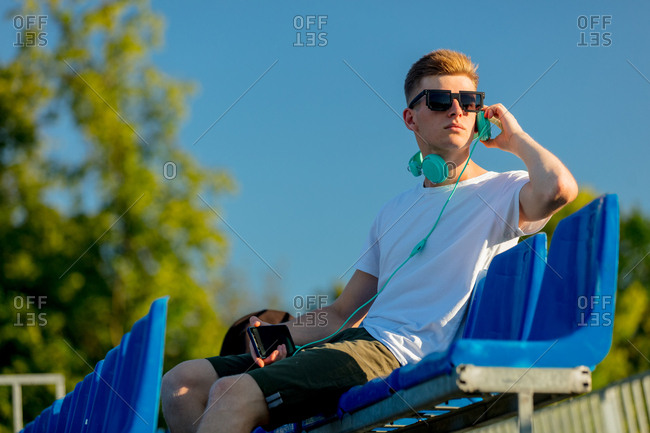 Young teen boy in sunglasses with headphones sitting in blue stadium seat