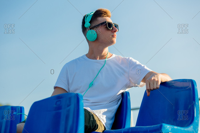 Young teen boy in sunglasses with headphones sitting in blue seat on stadium tribune