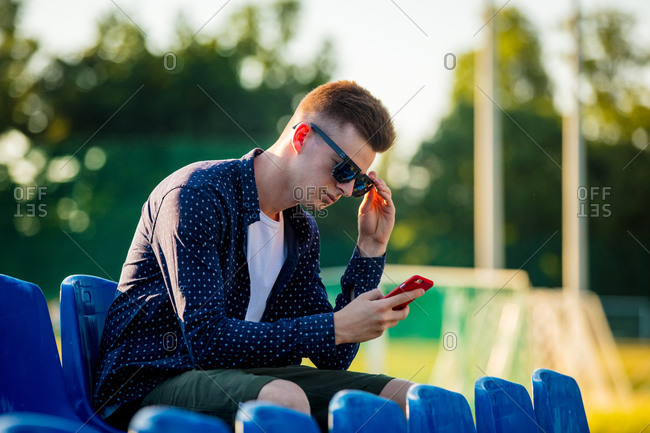 Young teen boy in sunglasses with mobile phone