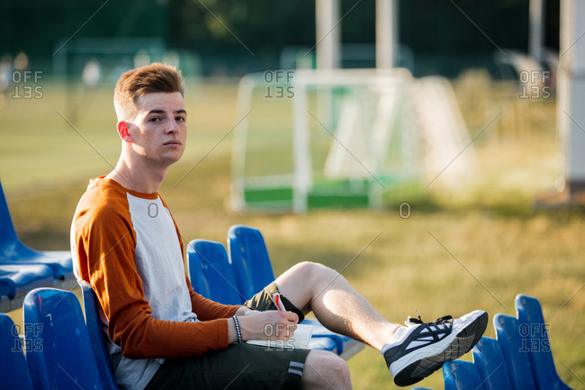 Portrait of teen boy with notebook and pencil sitting in blue seat on stadium tribune