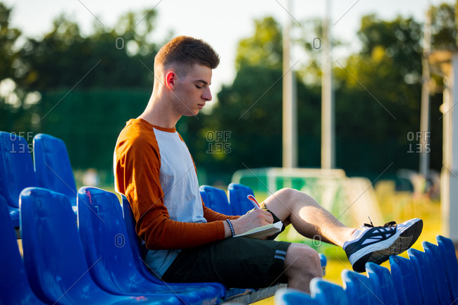 Young teen boy with notebook and pencil sitting in blue seat on stadium tribune