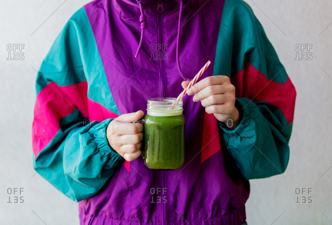 Woman in nineties style jacket holding a glass with celery juice