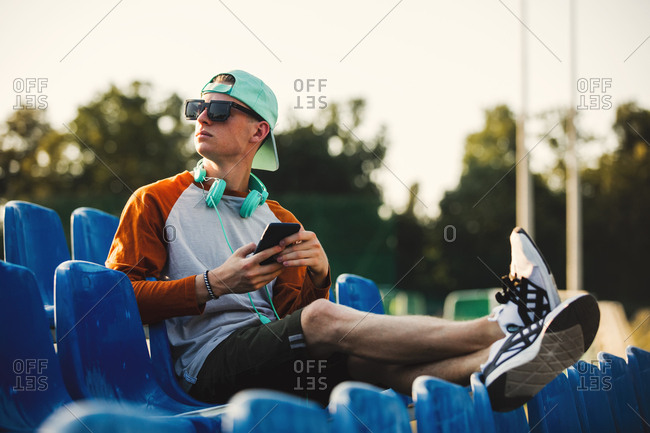 Young teen boy in sunglasses with headphones sitting in blue sit on stadium tribune