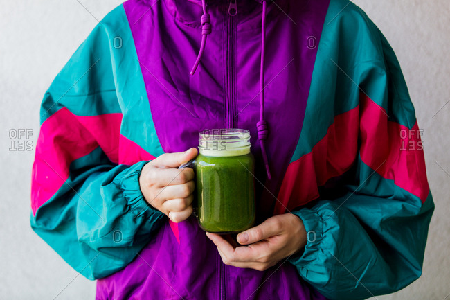 Woman in colorful jacket holding a glass with celery juice