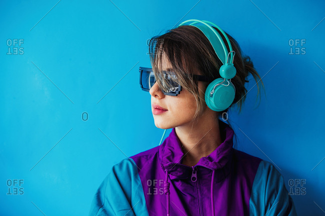 Young woman in nineties style jacket and with headphones