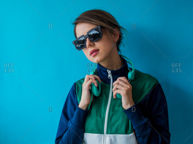 Portrait of a young woman in nineties style jacket and with headphones