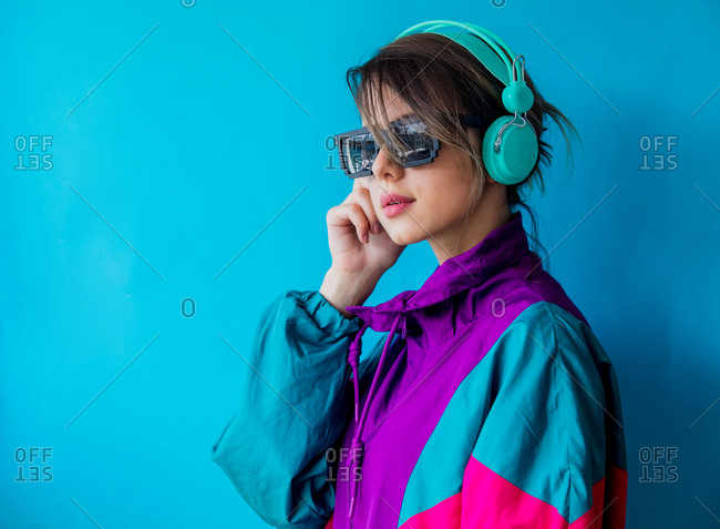 Young woman in colorful windbreaker jacket and with headphones