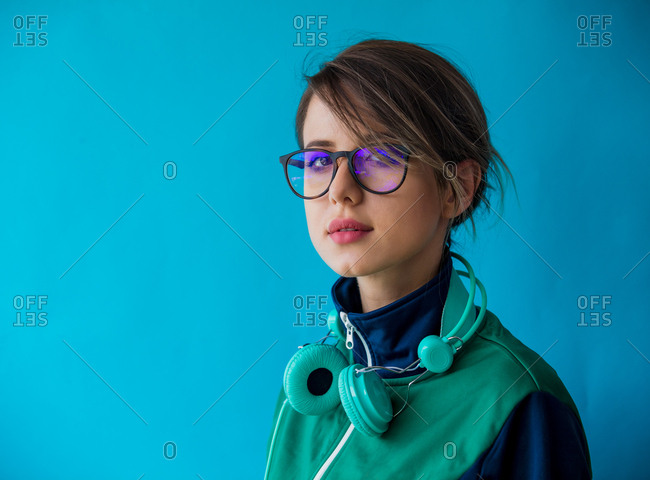 Portrait of a young woman in nineties style athletic jacket and with headphones