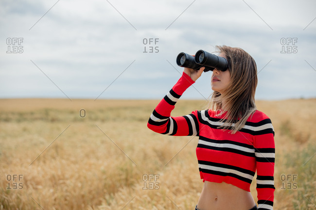 Young woman in red sweater with binoculars in a wheat field
