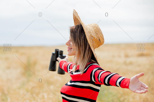 Young woman in red sweater and sun hat with binoculars in a wheat field