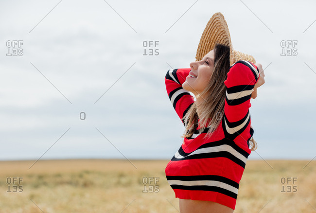 Young woman in red sweater and sun hat in a wheat field