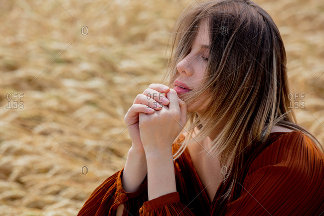 Woman wearing brown top sitting in a wheat field with eyes closed