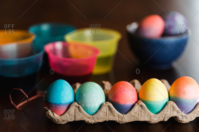 Colorful Easter eggs and dye containers on a wooden table.