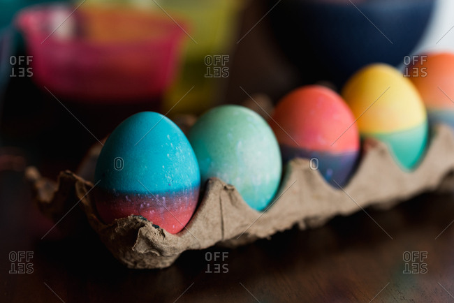 Row of brightly dyed Easter eggs in a carton on a table.