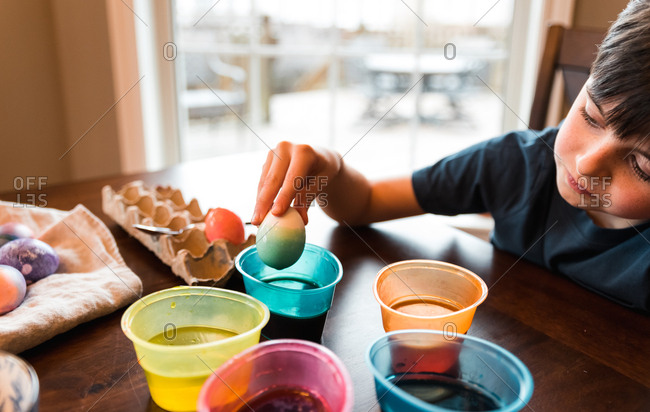 Boy dipping an egg in a container of dye to color it for Easter.