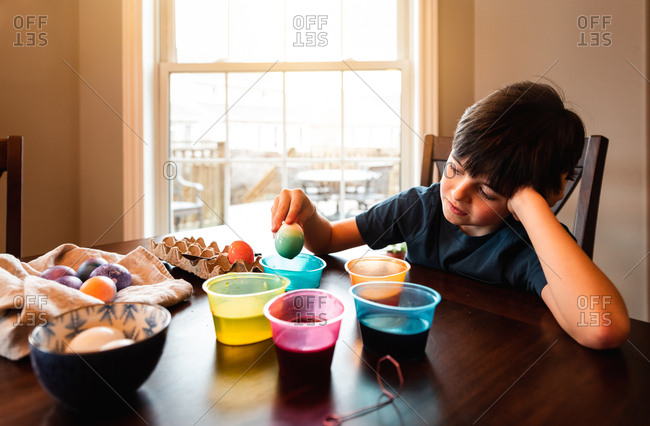 Young boy coloring Easter eggs with containers of dye at the table.