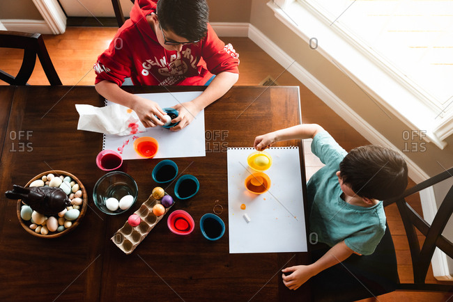 High angle shot of two boys dying colorful Easter eggs at table.