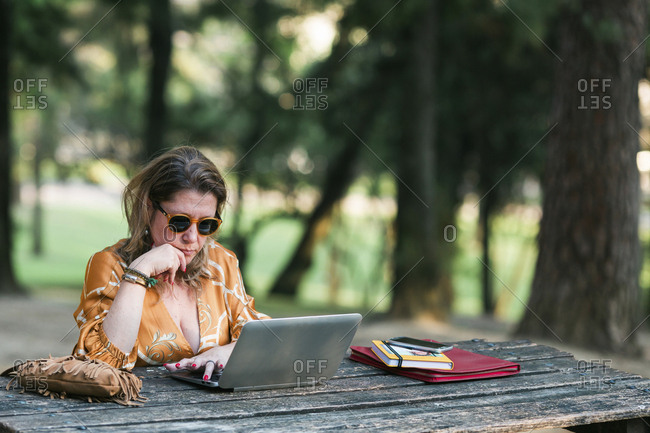 Woman using laptop outdoors, on wood table.