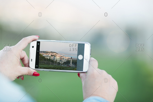 Woman photographing Lisbon with smartphone