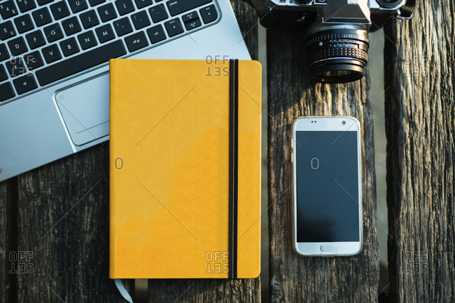Overhead view of yellow notebook and smartphone, by laptop and camera.