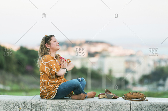 Woman meditating in city park