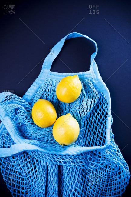 Top view of three lemons lying in turquoise net bag against black