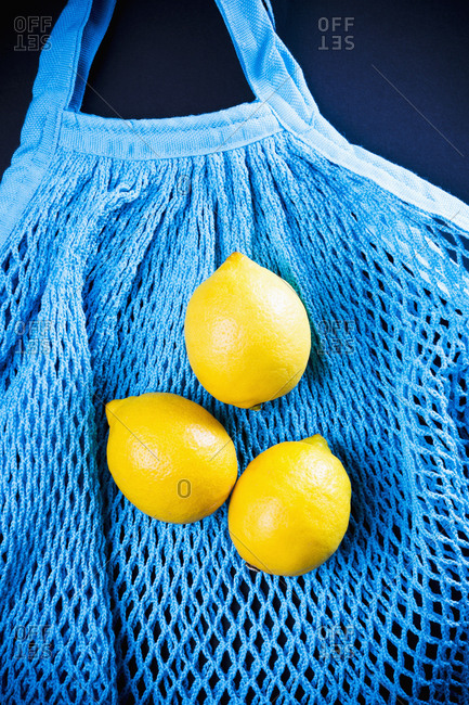 Top view of three lemons lying on turquoise net bag